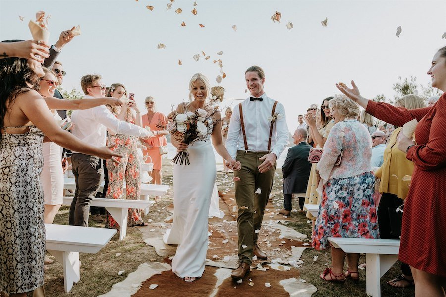 A bride and groom walk down the ailse and guests throw confetti