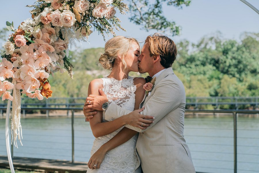 waterfront venue wedding ceremony with floral arbour