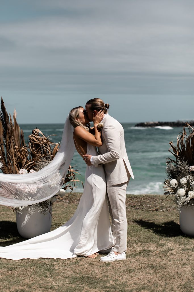 A bride and a groom kiss. You can see the beach in the background.