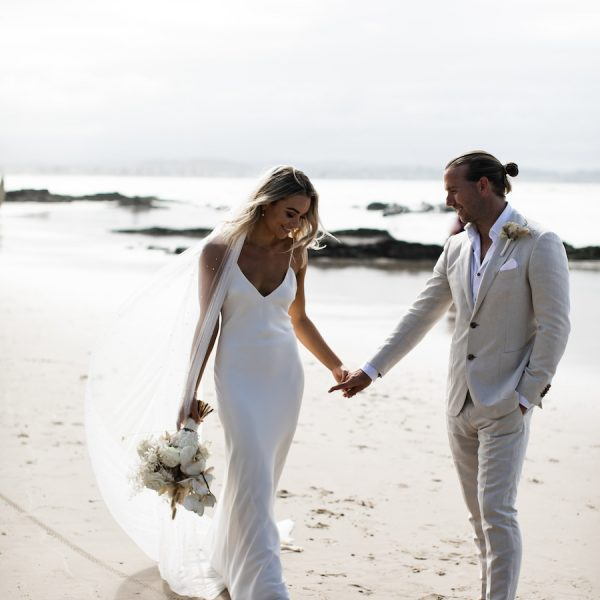 A bride and groom hold hands on the beach