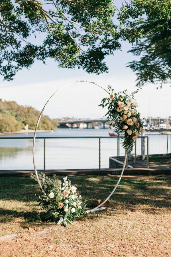 A circular arbour with white and pink florals in the Ancora waterside garden