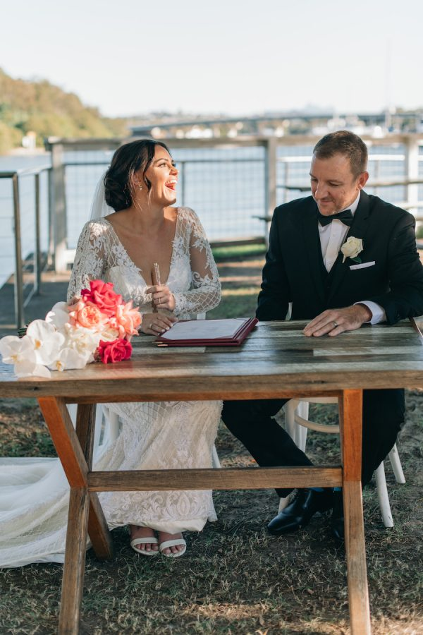 A bride and a groom sign their wedding papers in the Ancora waterside garden