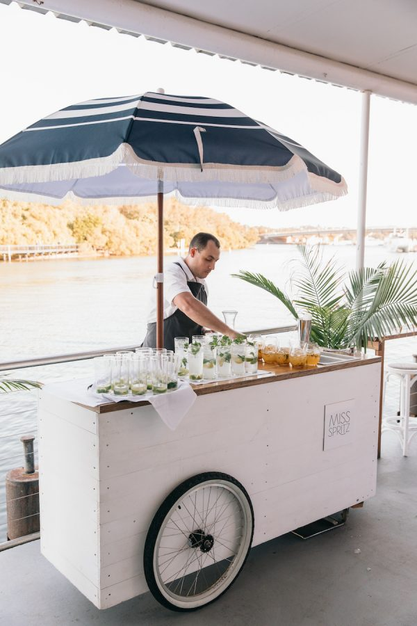 Miss Spritz cart at Ancora with a blue beach umbrella and drinks on the bar