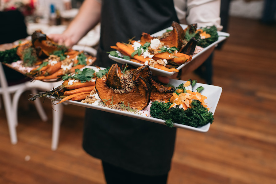 A wait person holds plates of wedding food from the menu